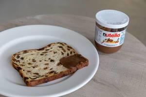 Früchtebrot, an einer Ecke mit Nutella bestrichen auf Teller neben Nutella-Glas