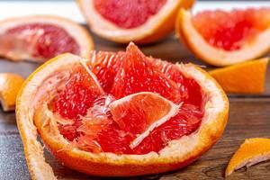 Fruchtfleisch von reifen Grapefruits, mit Schale, auf einem Holztisch