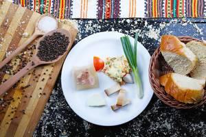 Frühstück-Idee aus der Balkanküche mit Speck, Schweinefleisch in Aspik, Lauch und Rindfleischsalat serviert mit Brot