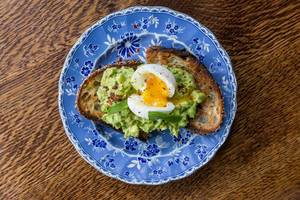 Frühstück mit Avocado, Ei, Basilikum, Limette, Chili und Mehrkornbrot auf einem blauen, blumendekorierten Teller, Aufnahme von Oben