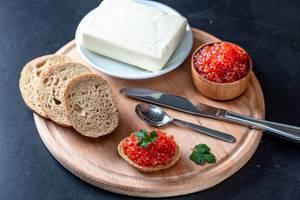 Frühstück mit Brot, Butter und rotem Kaviar auf einem Brettchen