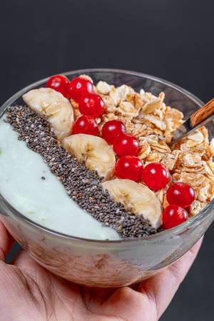 Frühstück mit Haferflocken und Früchten in einer Glasschale in der Hand einer Frau