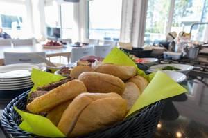 Frühstücksbüffet mit aufgeschnittenen Brötchen in einem blauen Korb im Hotel