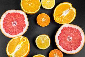 Fruit background with half a grapefruit, orange, lemon and mandarin on a black background, top view (Flip 2020)