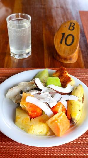 Fruit salad with banana, pineapple, coconut and papaya with a glass of water on orange-red dish pad