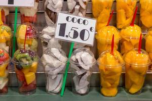 Fruit salad with coconut, kiwi, mango and melon is sold as streetfood in plastic boxes at indoor market Mercat de la Boqueria in Barcelona, Spain