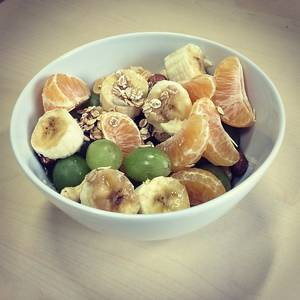Fruits and oats for breakfast at home - bananas, mandarines and grapes