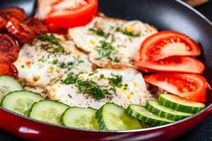 Frying pan with fried eggs and fresh vegetables with herbs