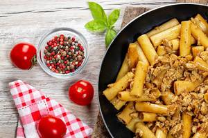 Frying pan with pasta and chicken on a wooden background with spices and fresh tomatoes