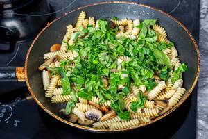Frying pan with pasta, mushrooms and herbs on the electronic hob (Flip 2019)