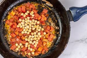 Frying sliced Tomato with Chickpeas in the frying pan