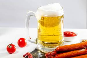 Full glass of light beer with foam and sausages on white table (Flip 2019)