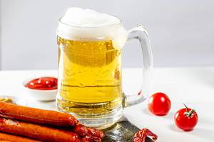 Full glass of light beer with foam and sausages on white table