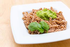 Full grain fussili pasta with green pesto and basil leaves