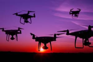 Fünf Drohnen am Abendhimmel schwebend