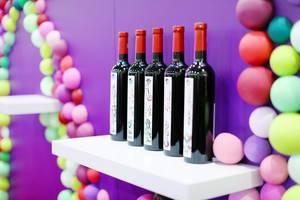 Fünf Flaschen Wein auf einem weißen Regal vor feierlichem Hintergrund