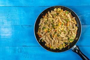 Fusilli-Nudeln mit Gemüse gebraten in einer Pfanne auf einem blauen Holztisch Draufsicht