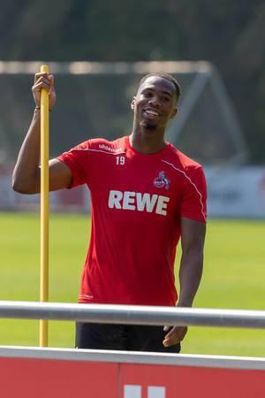 Fußballer Kingsley Ehizibue mit Trainingsutensilien in der Hand, lacht fröhlich in die Kamera