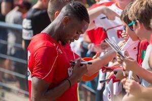 Fußballer Kingsley Ehizibue unterschreibt sein eigenes Trikot und unterhält sich mit jungen Fußballfans und Kindern