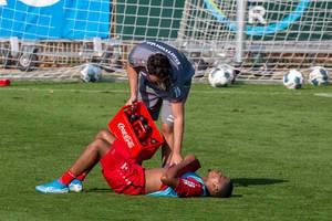 Fußballer Leon Bailey liegt erschöpft auf dem Rasen, Trainer kühlt ihn mit Coca Cola Flaschen