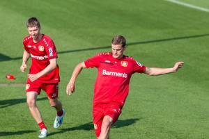Fußballer Mitchell Weiser und Sven Bender laufen beim Fußballtraining über das Spielfeld
