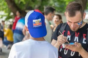Fußballfans schminken ihre Gesichter