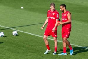 Fußballspieler in roten Trainingstrikots: Lars Bender und Karim Bellarabi unterhalten sich auf dem Fußballfeld, während der Trainingspause