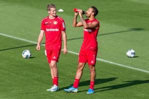 Fußballspieler Karim Bellarabi trinkt aus einer Coca Cola Trinkflasche, neben lachendem Lars Bender
