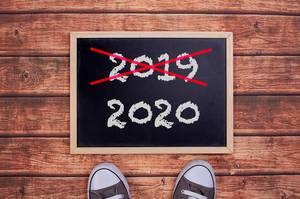 Füße vor einer Jahreszahltafel symbolisieren den Übergang und Eintritt in das Jahr 2020