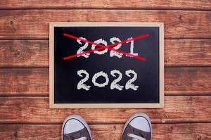 Füße vor einer Jahreszahltafel symbolisieren den Übergang und Eintritt in das Jahr 2022