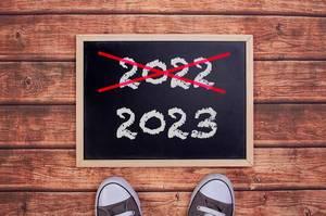 Füße vor einer Jahreszahltafel symbolisieren den Übergang und Eintritt in das Jahr 2023