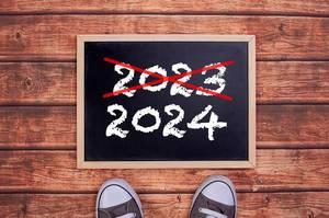 Füße vor einer Jahreszahltafel symbolisieren den Übergang und Eintritt in das Jahr 2024
