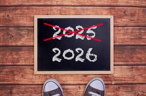 Füße vor einer Jahreszahltafel symbolisieren den Übergang und Eintritt in das Jahr 2026