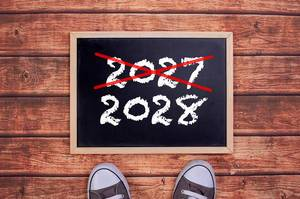 Füße vor einer Jahreszahltafel symbolisieren den Übergang und Eintritt in das Jahr 2028