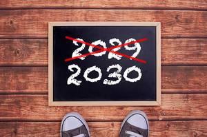 Füße vor einer Jahreszahltafel symbolisieren den Übergang und Eintritt in das Jahr 2030