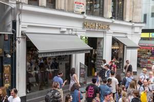 Fußgänger laufen an einem Shake Shack Lokal vorbei