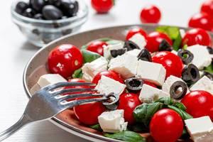 Gabel und Salat mit Basilikum, Tomaten, Oliven und Feta-käse in der Nahaufnahme