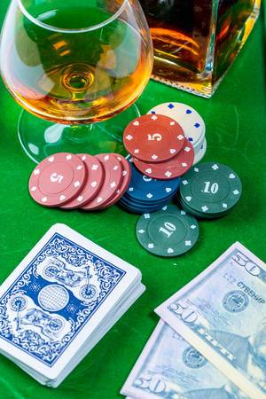 Gambling - cards with chips and alcohol on the green poker table
