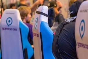 Gamer sitzen in Gamescom Gaming-Sesseln