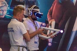 Gamer with PlayStation VR Headset and Aim Controller at Gamescom