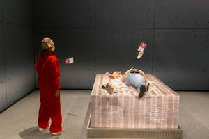 Games fair visitors lie on piles of money of Netflix TV Show Money Heist / La casa de papel at the Gamescom in Germany