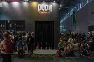 Games fair visitors waiting in line with camping chairs, to play Doom Eternal during Gamescom