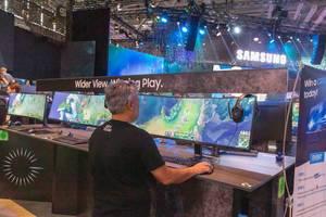 Gamescom-Messebesucher testet den Samsung CRG9 49 Zoll Gamingbildschirm, mit gekrümmtem und ultraweitem Bildseitenverhältnis