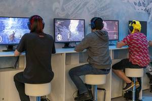 Gamescom visitors playing the Action-Adventure videogame Monster Hunter World Iceborne next to each other