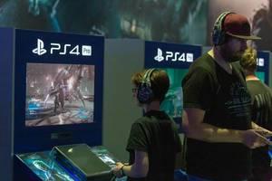Gamescombesucher testen Neuerscheinungen der Videospielbranche auf der PS4 Pro / PlayStation 4 Pro