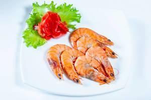 Ganze gekochte Garnelen mit eingelegtem Ingwer auf Salatblatt auf weißem Teller