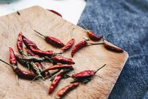 Ganze, getrocknete, rote Chilis auf Holzbrett