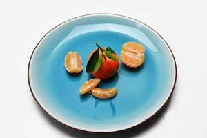 Ganze Mandarine mit Blättern im Zentrum und geschälte und geteilte Frucht daneben auf blauem Teller