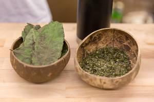 Ganze und gemahlene Guya-Blätter in Kokosschälchen als Anschauung