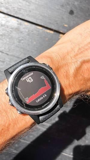 Garmin-Smartwatch an einem Männerarm zeigt mit Temperaturwidget die aktuelle Temperatur an